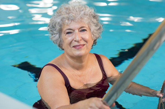 Smiling active senior woman entering in a swimming pool