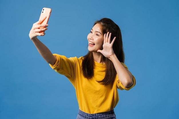 青の背景に分離されたカジュアルな服装とスタンドで肯定的な表現を持つスマートフォンでselfie写真を作る愛らしいアジア女性の笑みを浮かべてください。幸せな愛らしい喜んで女性は成功を喜ぶ。