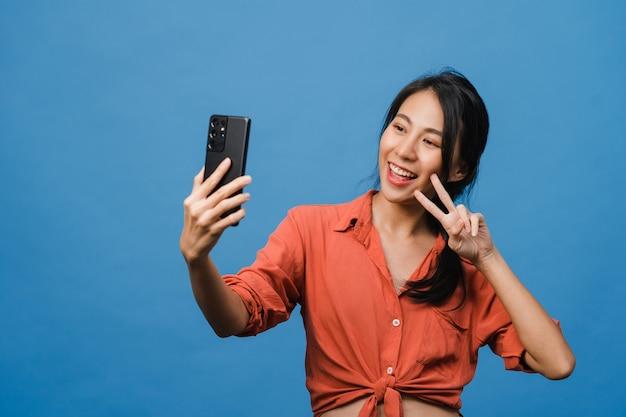 笑顔の愛らしいアジアの女性がカジュアルな服装でポジティブな表情でスマートフォンで自分撮り写真を作り、青い壁に隔離されたスタンド。幸せな愛らしい嬉しい女性は成功を喜んでいます。