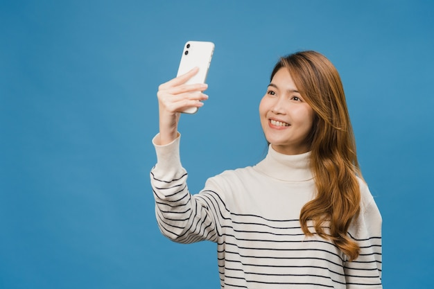 笑顔の愛らしいアジアの女性がカジュアルな服装でポジティブな表現と青い壁に隔離されたスタンドでスマートフォンで自分撮り写真を作る
