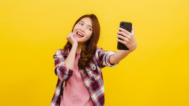カジュアルな服装で肯定的な表情でスマートフォンで自分撮り写真を作る愛らしいアジアの女性の笑顔と黄色の壁越しにカメラ目線。幸せな愛らしい喜んで女性は成功を喜ぶ。