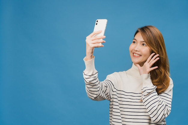 Smiling adorable asian female making selfie photo on smart phone with positive expression in casual clothing and stand isolated on blue wall