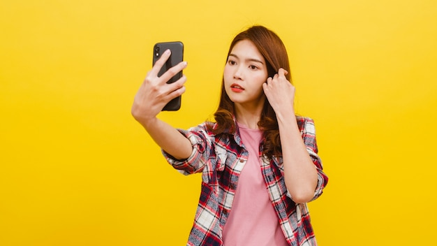 Smiling adorable asian female making selfie photo on smartphone with positive expression in casual clothing and looking at camera over yellow wall. happy adorable glad woman rejoices success.