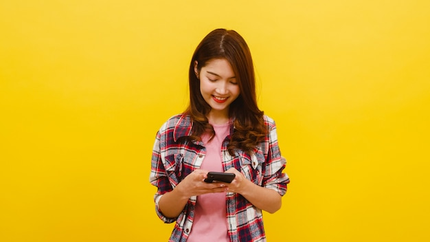 Smiling adorable asian female using phone with positive expression, smiles broadly, dressed in casual clothing and looking at camera over yellow wall. happy adorable glad woman rejoices success.