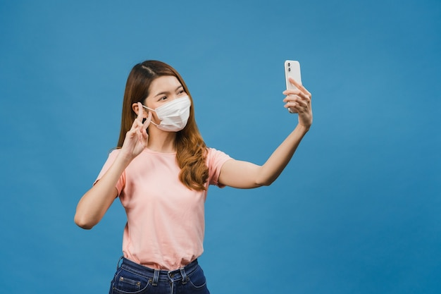 Smiling adorable asian female wearing medical face mask making selfie photo on smart phone with positive expression in casual clothing and stand isolated on blue wall