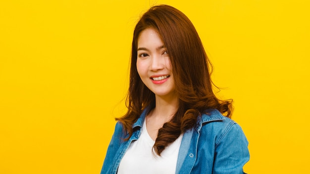 Smiling adorable asian female with positive expression, smiles broadly, dressed in casual clothing and looking at the camera over yellow wall. happy adorable glad woman rejoices success.