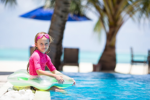 Smiling adorable girl having fun in outdoor swimming pool