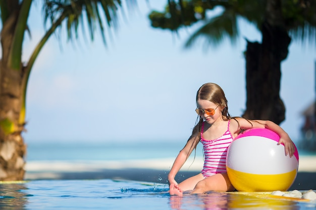 Smiling adorable girl playing with inflatable toy ball in outdoor swimming pool