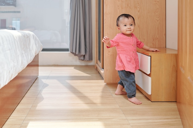 Smiling adorable little girl exploring apartment and walking in bedroom of her parents