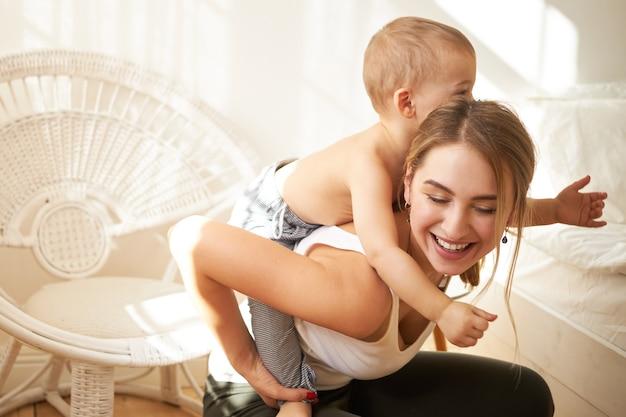 Улыбающаяся очаровательная девочка-подросток присматривает за маленьким мальчиком, подбивая его домой. радостная молодая мать скачет на спине своего милого сына, наслаждаясь вместе в помещении, весело проводя время