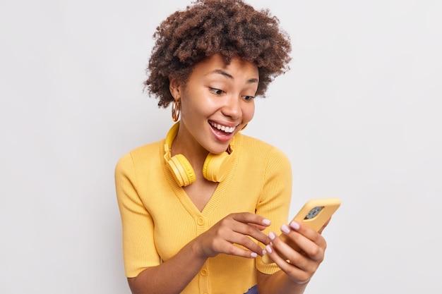 Улыбающаяся очаровательная девочка-подросток с кудрявыми волосами болтает онлайн через смартфон, использует приложение, пристрастие к современным технологиям, носит стереонаушники на шее, повседневный желтый джемпер, белая стена
