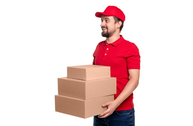 Smiling adult bearded male courier in red shirt and cap delivering stack of parcels in carton packages