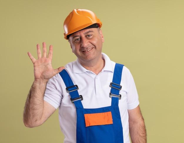 Sorridente uomo costruttore adulto gesti cinque isolati sulla parete verde oliva