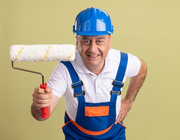 유니폼에 웃는 성인 작성기 남자 보유 올리브 그린에 롤러 브러시