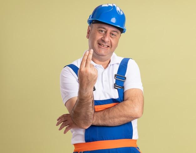 Sorridente uomo adulto costruttore in uniforme gesti due con le dita su verde oliva
