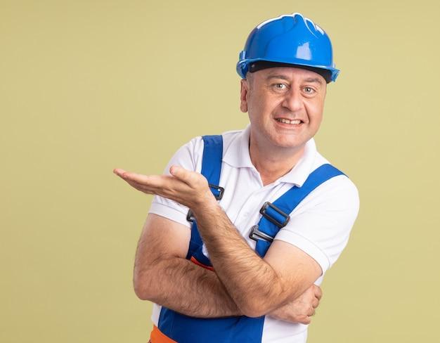 Sorridente uomo adulto costruttore in uniforme tiene la mano aperta su verde oliva