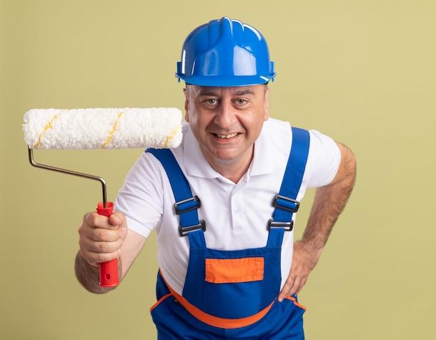 L'uomo adulto sorridente del costruttore in uniforme tiene la spazzola del rullo su verde oliva