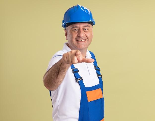 Uomo adulto sorridente del costruttore in sguardi uniformi e punti alla macchina fotografica su verde oliva