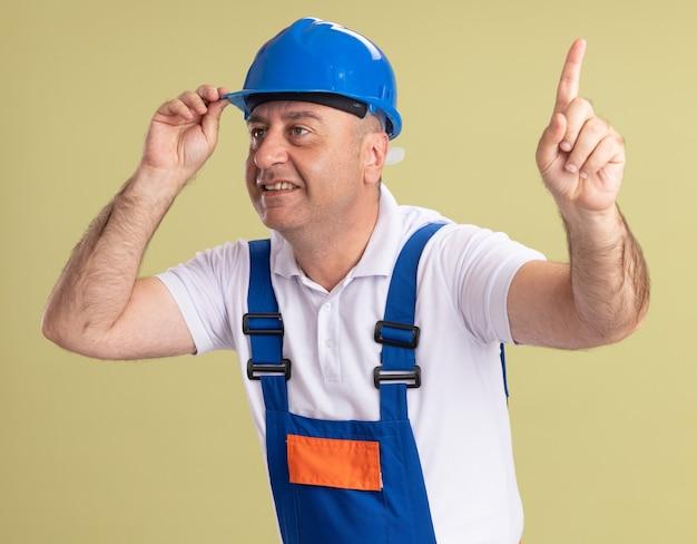 L'uomo adulto sorridente del costruttore in uniforme esamina il lato e indica in alto isolato sulla parete verde oliva