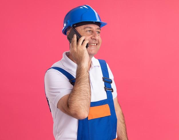 Uomo adulto sorridente del costruttore in colloqui uniformi sul telefono che esamina il lato isolato sulla parete rosa