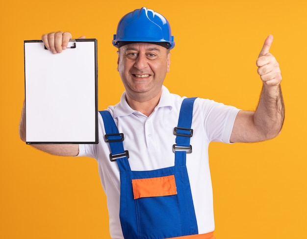 Sorridente uomo costruttore adulto in uniforme pollice in alto e tiene appunti isolato sulla parete arancione