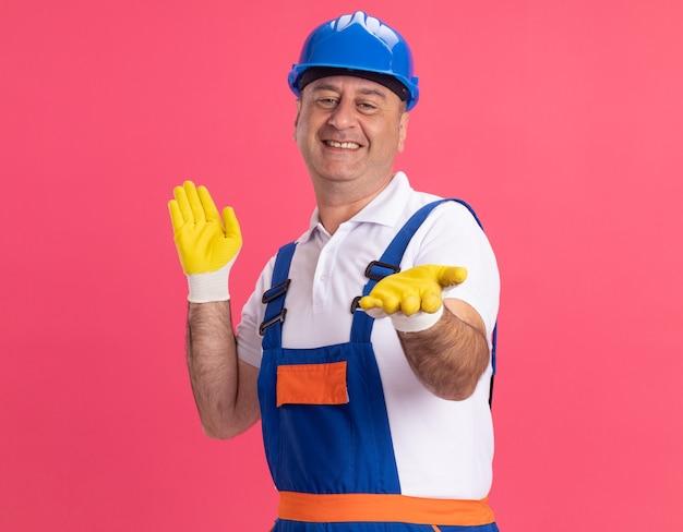 Sorridente uomo costruttore adulto in uniforme che indossa guanti protettivi tiene le mani aperte isolate sulla parete rosa