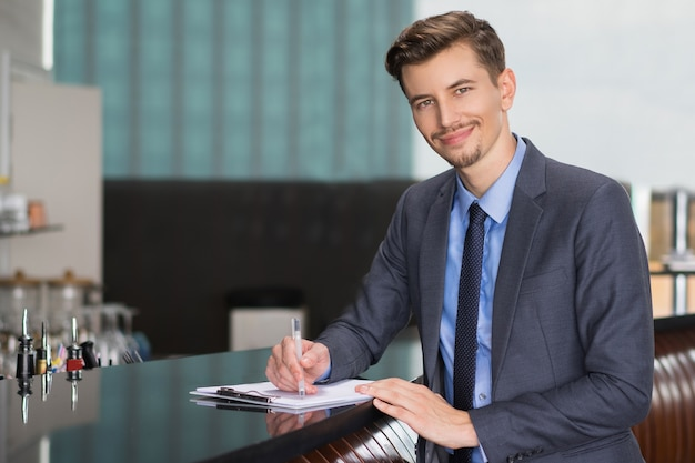 Smiling adult businessman writing at cafe counter