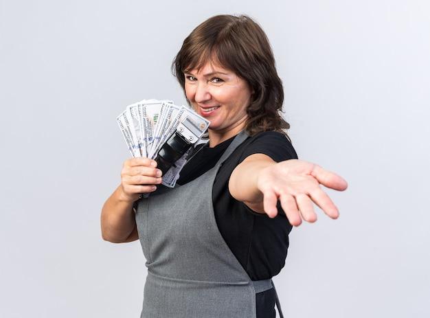 Sorridente barbiere femmina caucasica adulta in uniforme che tiene tagliacapelli con soldi e allungando la mano isolata sul muro bianco con spazio copia