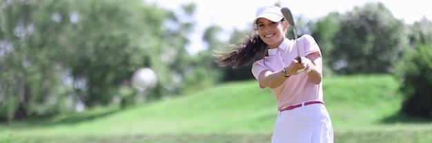 공 초상화에 타격하는 골프 클럽에서 웃는 성인 백인 여자.