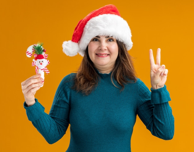 Улыбающаяся взрослая кавказская женщина в шляпе санта-клауса держит конфету и жестикулирует знак победы на оранжевом фоне с копией пространства