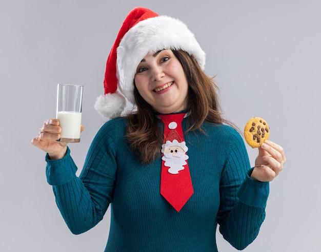 La donna caucasica adulta sorridente con il cappello della santa e il legame della santa tiene il bicchiere di latte e il biscotto isolato su fondo bianco con lo spazio della copia