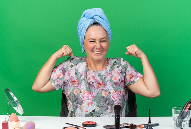 Sorridente donna caucasica adulta con i capelli avvolti in un asciugamano seduto al tavolo con strumenti per il trucco tendendo i suoi bicipiti isolati sulla parete verde con spazio di copia