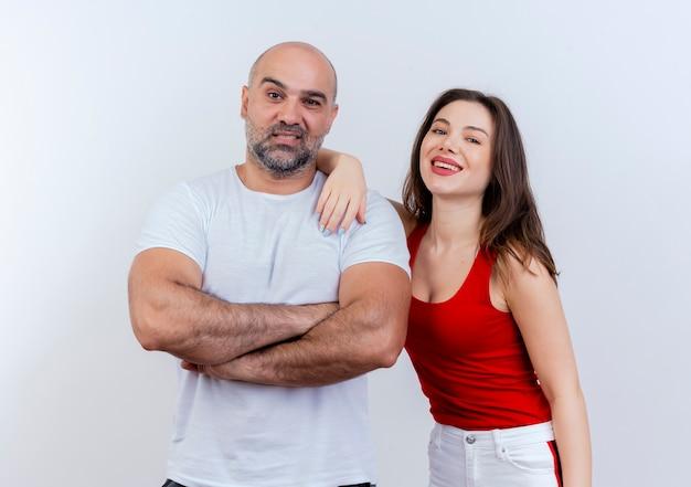 Uomo adulto sorridente delle coppie che sta con la postura chiusa e la donna che mette la mano sulla sua spalla entrambi alla ricerca
