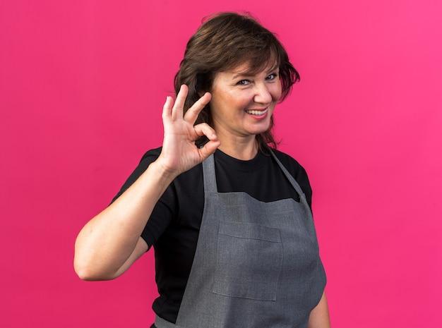 Sorridente femmina adulta barbiere in uniforme gesticolando segno ok isolato sulla parete rosa con copia spazio