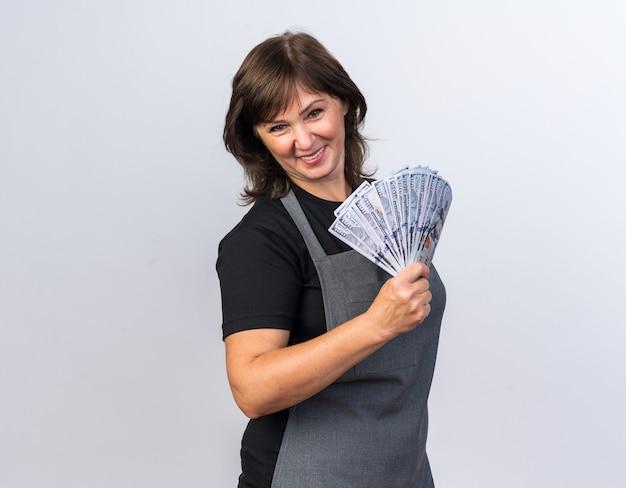 Sorridente femmina adulta barbiere in uniforme tenendo soldi isolati sul muro bianco con copia space