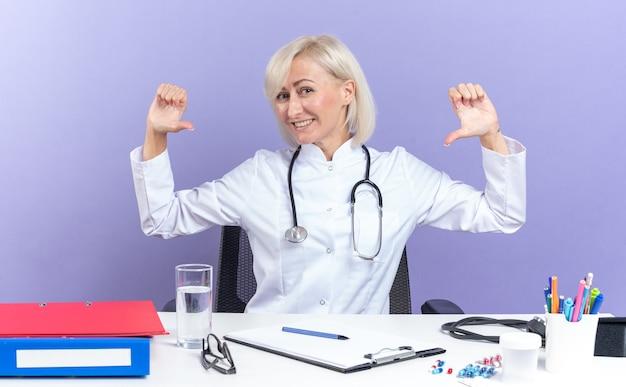 의료 가운을 입은 웃고 있는 성인 여성 의사, 책상에 앉아 있는 청진기, 복사 공간이 있는 보라색 벽에 격리된 자신을 가리키는 사무실 도구