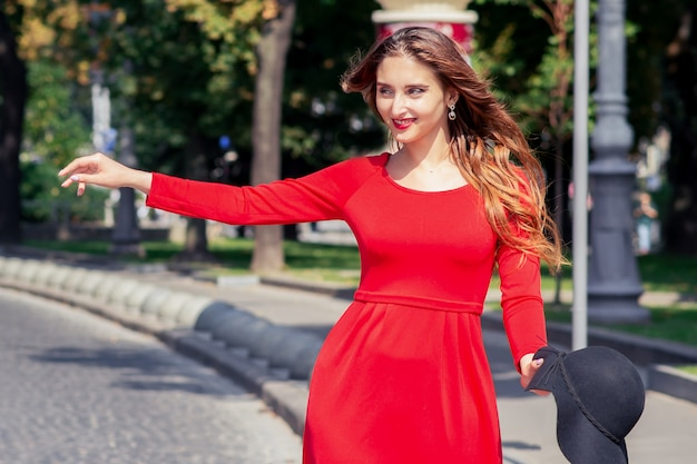 赤いドレスを着た笑顔の大人の女の子は、街でタクシーをキャッチしています。