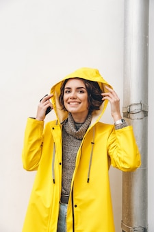 Smiling adult girl in yellow coat putting hood on head posing on camera with candid smile being happy