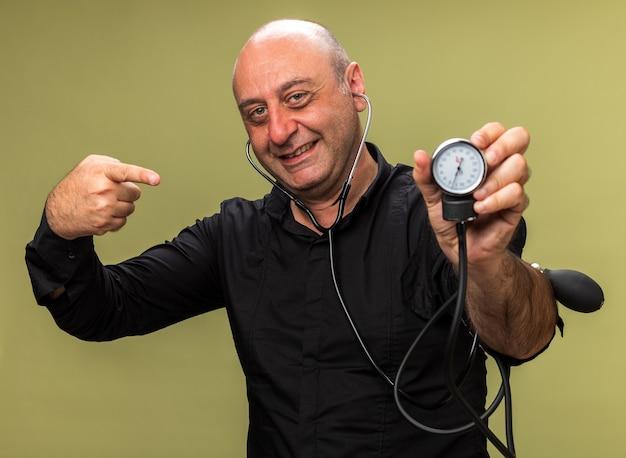 Sorridente adulto malato uomo caucasico tenendo e puntando allo sfigmomanometro isolato su parete verde oliva con spazio di copia