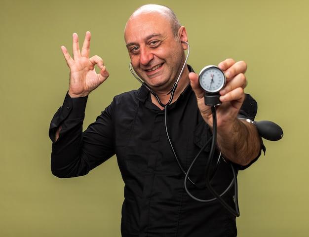 Sorridente adulto malato uomo caucasico tenendo lo sfigmomanometro e gesticolando segno ok isolato sul verde oliva parete con spazio di copia