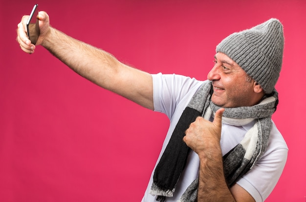 Smiling adult ill caucasian man with scarf around neck wearing winter hat thumbs up looking at phone taking selfie isolated on pink wall with copy space
