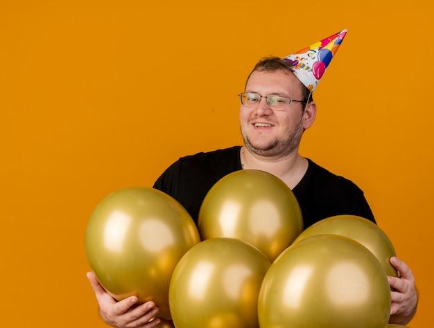 Sorridente uomo adulto in occhiali da vista che indossa il cappello di compleanno sta con palloncini di elio isolati sulla parete arancione