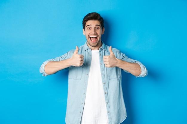 Uomo adulto sorridente che mostra i pollici in su con la faccia eccitata, come qualcosa di fantastico, che approva il prodotto, in piedi su sfondo blu. Foto Gratuite