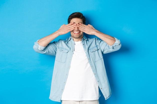Sorridente uomo adulto in attesa di sorpresa, coprendosi gli occhi con le mani e anticipando, in piedi su sfondo blu in abiti casual