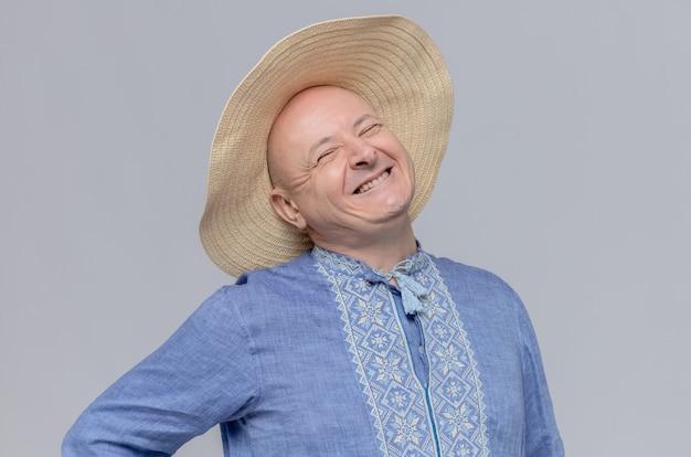 Uomo adulto sorridente con cappello di paglia e in camicia blu che guarda