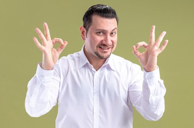 Sorridente uomo d'affari slavo adulto gesticolando segno ok