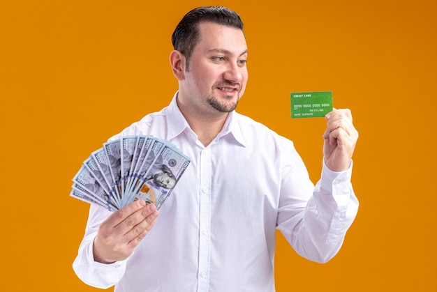 Smiling adult slavic businessman holding money and looking at credit card