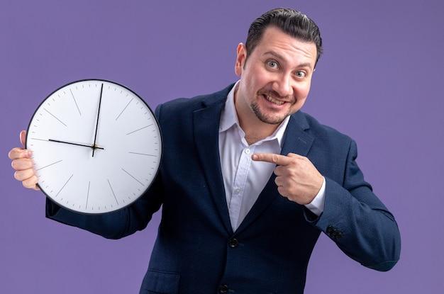 Sorridente uomo d'affari slavo adulto che tiene e indica l'orologio