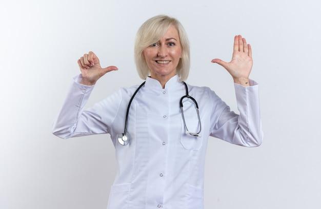 Улыбающаяся взрослая славянская женщина-врач в медицинском халате со стетоскопом, указывая на ее руку, изолированную на белом фоне с копией пространства