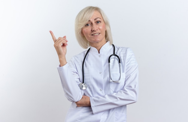 Sorridente medico femmina slava adulta in abito medico con stetoscopio rivolto verso l'alto isolato su sfondo bianco con spazio copia